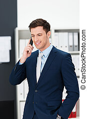 Stylish young businessman taking a call on a mobile phone standing listening to the conversation with a thoughtful expression and his hand in his pocket