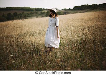 Stylish girl in linen dress walking among herbs and wildflowers in meadow. Boho woman relaxing in countryside, simple slow life style. Atmospheric image. Space text
