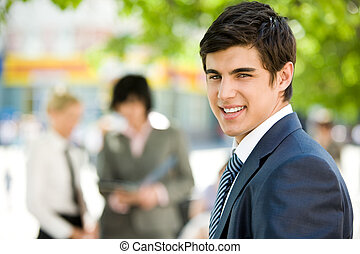 Portrait of confident businessman smiling at camera in a natural environment