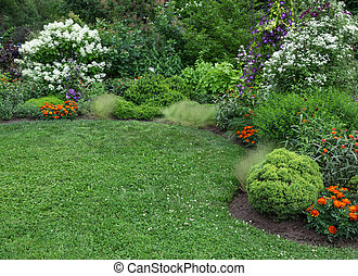 Beautifully landscaped summer garden with green lawn.