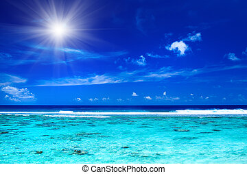 Sun and sky over tropical ocean with vibrant colors