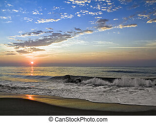 The sun rises over sea surf with reflections and clouds.