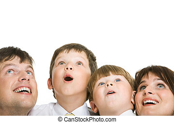 Photo of surprised family members looking upwards with excitement