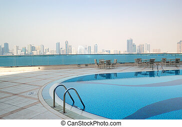 Swimming pool with Sharjah fountain and man-made lake view at the luxury hotel, Sharjah, UAE