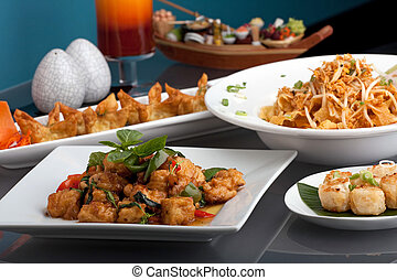 A big assortment of Thai foods and appetizers presented beautifully with fancy garnish.