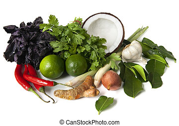 Ingredients for Thai food, ready for cooking. Includes purple basil, coriander or cilantro, coconut, lemon grass, garlic, kaffir lime leaves, shallots, limes, red chilli peppers, and galangal.