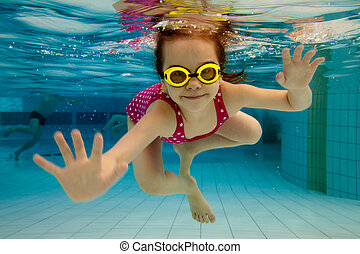 The little girl in the water park swimming underwater and smiling