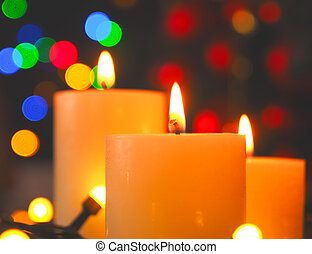 Three burning Advent candles with Christmas lights