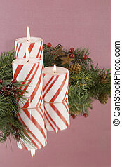 three striped Christmas candles soft background
