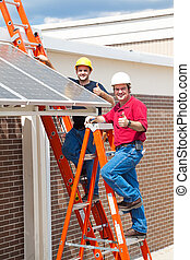 Two workers installing solar panels and giving the thumbs up sign.