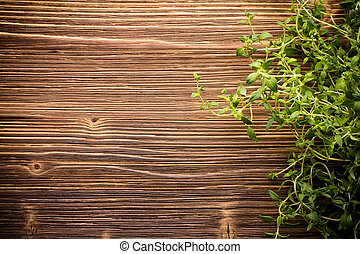Thyme and wooden textured background.