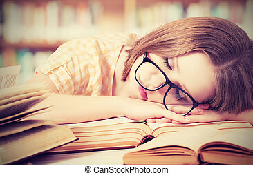tired student girl with glasses sleeping on the books in the library