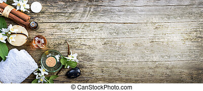 Top view of essential oils with jasmine, cinnamon and vanilla on rustic wooden table with copyspace. Spa and wellness aromatherapy treatment.