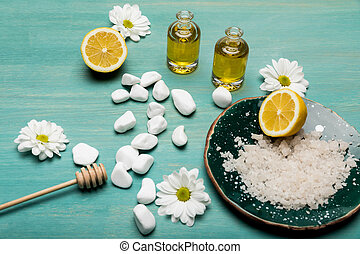 Top view of sea salt, oil in bottles, sliced lemon and chamomiles on wooden table top