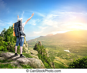 Tourist with backpack enjoy valley view from top of a mountain