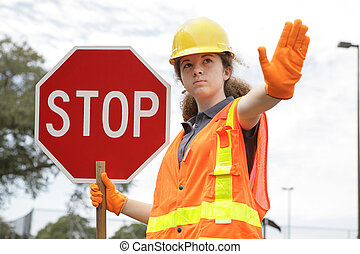 A female construction worker holding a stop sign.