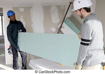 Two builders carrying plasterboard