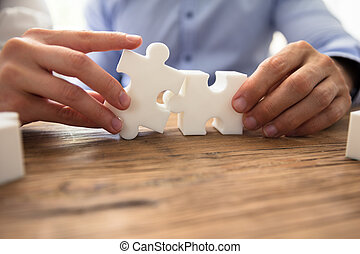 Two Businesspeople Connecting Jigsaw Pieces