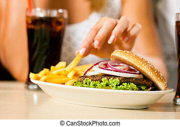A woman eating hamburger and drinking soda in a fast food diner; focus on the meal