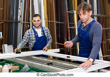 Two workmen working with window profiles at indusrty plant