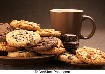 Assorted cookies in brown plate and brown mug of coffee on brown canvas.