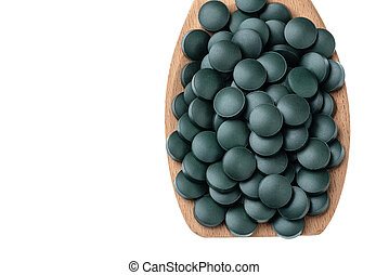 Vitamin and mineral supplements for vegetarians spirulina in tablets in a wooden spoon, close-up.