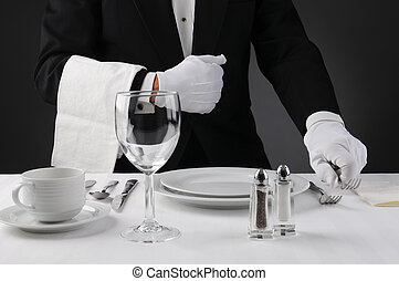 Closeup of a waiter in a tuxedo setting a formal dinner table. Shallow depth of field in horizontal format on a light to dark gray background. Man is unrecognizable.