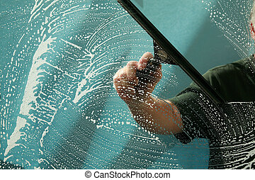 a window washer squeegiee cleans a window while window washing