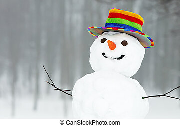 one winter snowman with coloured top hat standing in forest outdoors