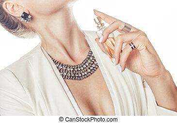 Woman applying perfume on her neck