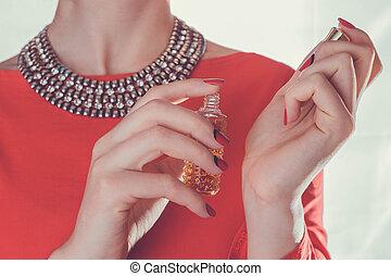 Woman applying perfume on her wrist