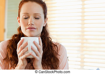 Woman enjoys the smell of her fresh coffee