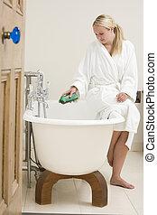Woman in bathroom putting bubble bath in bathtub