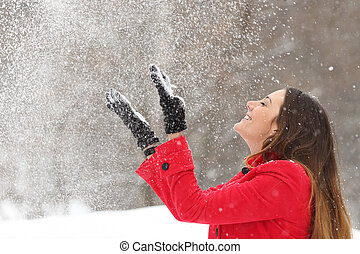 Woman in red throwing snow in the air in winter