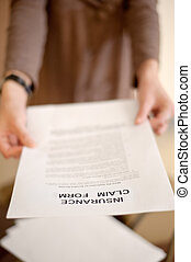 Woman showing insurance claim form to you, shallow DOF.