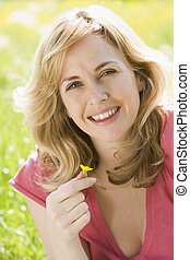 Woman sitting outdoors holding flower smiling