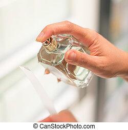 Woman testing perfume in the shop.