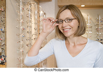 Woman trying on eyeglasses at optometrists smiling