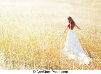 woman walking in the sunny meadow on summer day touching grass