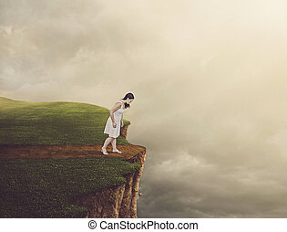 Woman walking on path that leads to a tall cliff.
