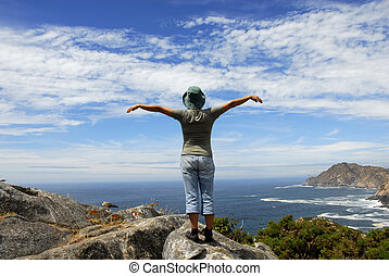 woman with arms wide open at the coast