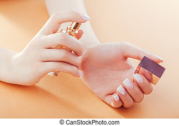 Woman with french ombre manicure applies perfume on her wrist. Scincare. Cosmetics