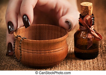 woman's hand with a bottle of essential oil