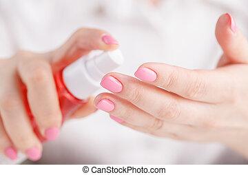 Woman`s hands spraying perfume