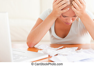 Despaired blond woman accounting in the living room