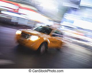 Yellow cab speeding through New York at night.
