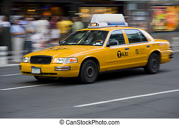 New York City yellow taxi cab in motion on a colorfull street