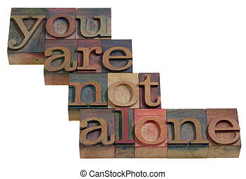 you are not alone - words in vintage wooden letterpress printing blocks, stained by color inks, isolated on white