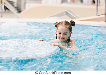 Young girl swimming in a hot tub.