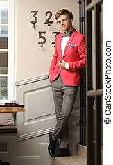 Full length young handsome stylish man fashion model wearning bright red jacket and bow tie posing indoor
